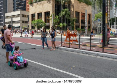Crowds walking and looking at performances in Paulista Avenue on Sunday afternoon. Paulista Avenue is closed for vehicles every Sunday. Sao Paulo, Brazil. 02/24/2019