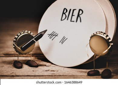 Crown cork miniature figures with a pen and a beermat, german word bier which means beer and tally or check list, humorous conceptual scene for traditional tavern or pub bills and gastronomy