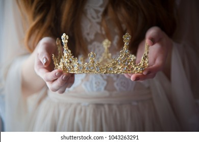 a crown in the hands of a girl