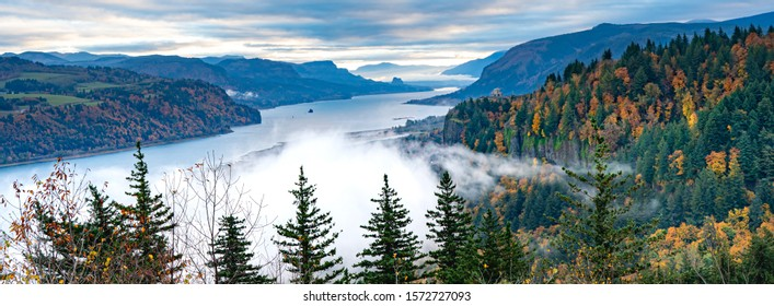 Crown Point, the vista house and the columbia River Gorge with fog, trees showing autumn colors, Oregon