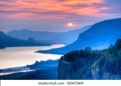 Crown Point and Vista House with rising sun over Columbia River Gorge.