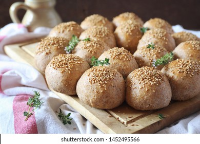 Crown sourdough bread buns with sesame and thyme garnish on wooden background