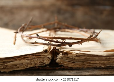 Crown of thorns and bible on old wooden background
