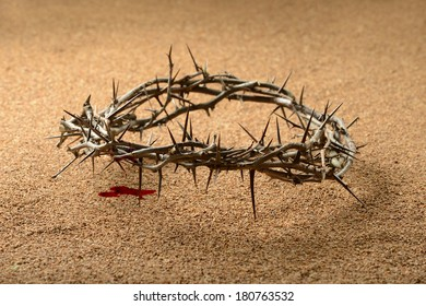 Crown of thorns with blood dripping on sand