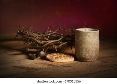Crown of thorns, cup of wine, bread and nails over wooden table