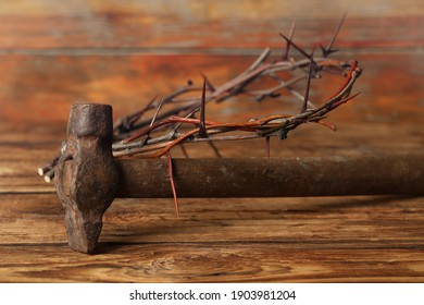 Crown of thorns and hammer on wooden table. Easter attributes