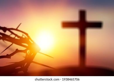 Crown of thorns of Jesus Christ against wooden catholic cross at sunset background