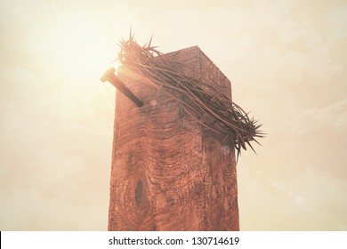 A crown of thorns and a nail atop a cross in sunlight.