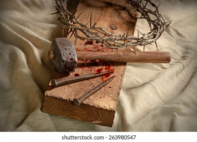 Crown of thorns, nails and hammer on wooden cross