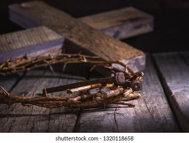 Crown of thorns and nails on a rustic wooden surface with a wood cross in background