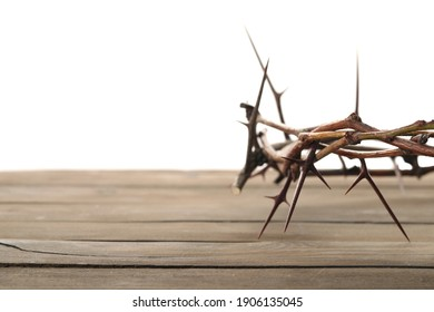 Crown of thorns on wooden table against white background, closeup with space for text. Easter attribute