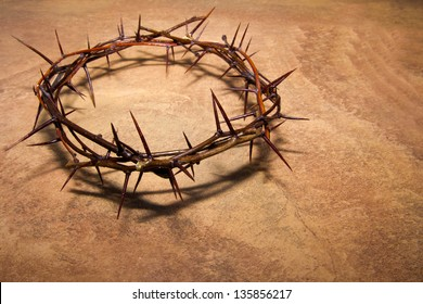 Crown of thorns over brown marble background, copy space. Christian concept of suffering.