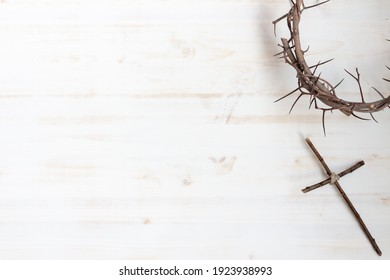 Crown of thorns with wood cross on white background with copy space