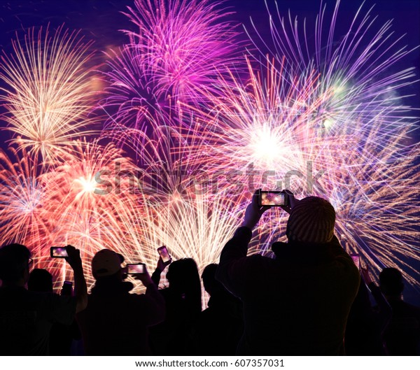 Crown watching colorful fireworks and recording on their cellphones