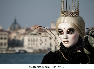 Crown and white venetian mask with beautiful eyes during Venice Carnival