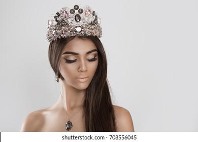 Crowned dark beauty queen. My hair is my treasure Brunette woman fashion model girl beautiful shiny makeup eyeshadow lipstick jewelry diamond crystal set earring necklace crown looking down eye closed