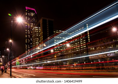 Croydon, England, CIRCA April 2019 - Traffic light trails from buses at night in Croydon in front of Safron Tower