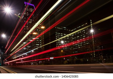Croydon, England, CIRCA April 2019 - Traffic light trails from buses at night in Croydon with Safron Tower in the background