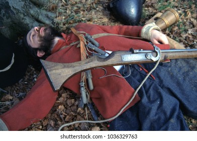 Croydon Surrey England 1996. A re-enactor of the English Civil War wears the historical uniform of a Musketeer he lays in a wood with a musket and equipment spread around him at a re-enactment event.