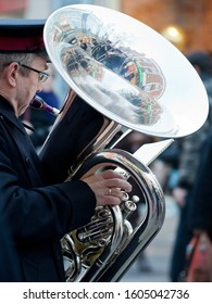 CROYDON, UK - DECEMBER 10, 2011: A tuba player in the Salvation Army brass band plays Christmas songs in North End, Croydon, UK. The tuba's bell reflects other band members and the surrounding shops.
