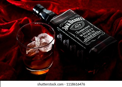 Croydon, UK - June 14, 2018: Illustrative editorial of  a bottle of Jack Daniel's bourbon whiskey on a dark red velvet background with dramatic light next to a glass of whiskey on the rocks