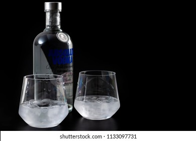 Croydon, UK - June 28, 2018: Illustrative editorial of a bottle of Absolut and two glasses of vodka on the rocks isolated against a dark black background with copy space