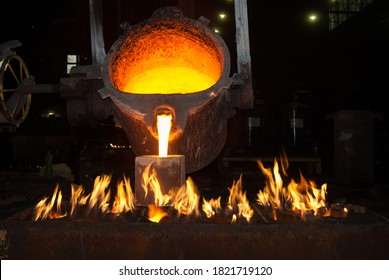 Crucible pouring molten iron into a vessel heated by flames in a foundry.
