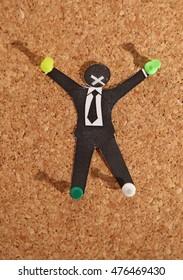 Crucified paper servant on corkboard