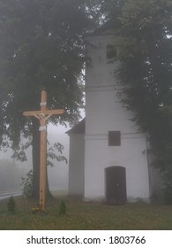 Crucifix and church in the fog
