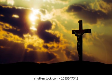 crucifix of Jesus Christ on the hill  against the light from cloudy sunset sky . can be use for Easter or Christian background, copy space