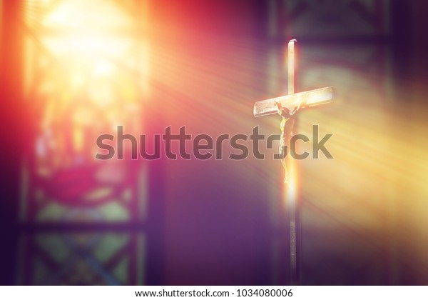 crucifix, jesus on the cross in church with ray of light from stained glass