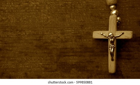 Crucifix of Jesus on the cross with wooden background. Symbol of christian religion and belief. Sepia. Place for text
