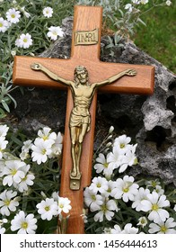 Crucifix laying in patch of small white  flowers. Concept that though our sins are as scarlet Jesus will make them white as snow