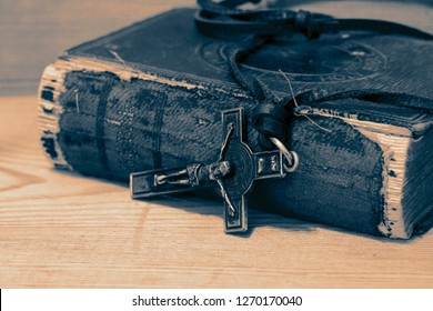 Crucifix necklace on a bible with wood background with colour toning