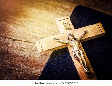 crucifix on old bible book on wooden background