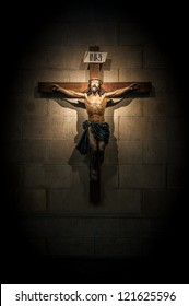 Crucifix on wall in spotlight inside old dark church or cathedral. Jesus Christ on cross. Religion, belief and hope. Holy and sacred places.