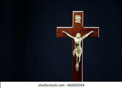 Crucifix, traditional christian crucifix presented on a plain black background.  Symbol representing the christian faith.