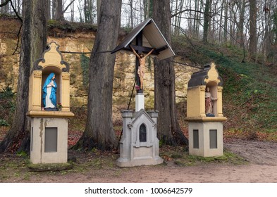 Crucifix under a wooden roof and two small chapels along the Geul river