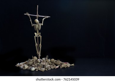 Crucifixion wooden skeleton top on pile of bone by god of death because perpetration of a sin on black background  / Still Life image and selective focus and space for message