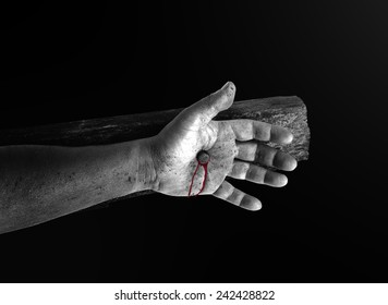 Crucify concept: Black and white bleeding Jesus christ hand with nail on wooden cross.
