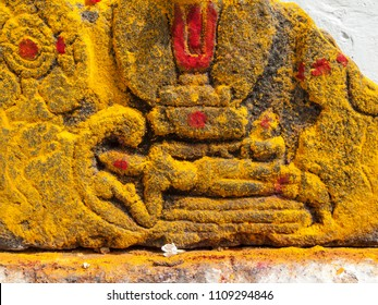 A crude carving of the Hindu god Vishnu covered in yellow turmeric powder at a temple in South India