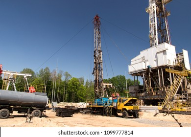 Crude oil and natural gas exploration and petroleum production drilling rigs and pump jacks, sand, trees and blue sky background