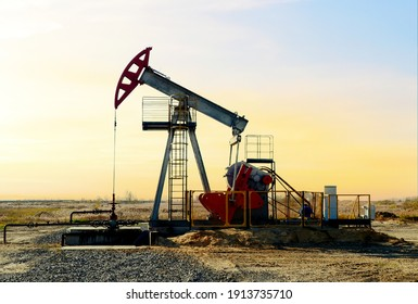 Crude oil pump jack at oilfield on sunset backround. Fossil crude output and fuels oil production. Oil drill rig and drilling derrick. Global crude oil Prices, energy, petroleum demand