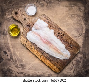 crude Pangasius on a cutting board with butter and salt on wooden rustic background top view close up