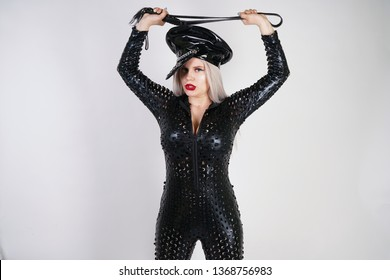 cruel fashionable bdsm lady with curves dressed in black catsuit with sexy holes and posing on a white background in the Studio