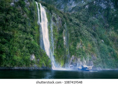 A cruise boat getting close to Stirling Falls at Milford Sound in Fiordland National Park, New Zealand, South Island.