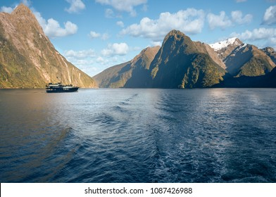 A cruise boat in the morning at Freshwater Basin in Milford Sound with Mitre Peak and numerous other Mountain Cliffs in Fiordland National Park, New Zealand, South Island.