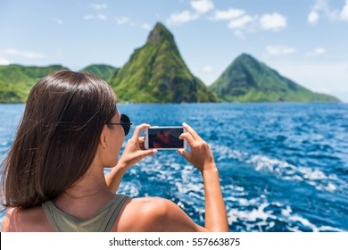 Cruise boat tourist taking mobile phone pictures of Deux pitons peaks, St-Lucia, Caribbean. The Gros and Petit Piton, world heritage site. Woman on shore excursion from ship in Castries, port of call.