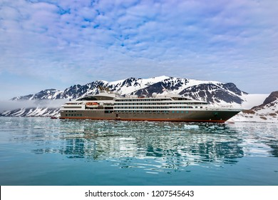Cruise expedition ship bow passing icy snow arctic waters near Spitsbergen, Svalbard, Norway