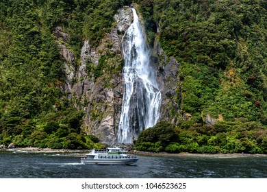 Cruise ferry and beautiful high waterfall in Milford Sound, Fiordland National park, New Zealand